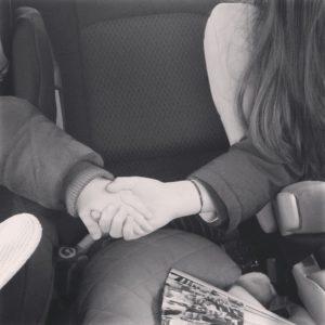 Enfants se tenant la main en voiture